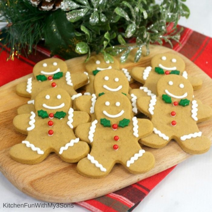 Cutting board with gingerbread man cookies in front of holiday decorations