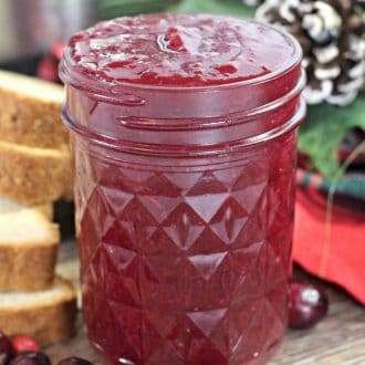 Instant Pot Cranberry Butter in a mason jar next to holiday decorations