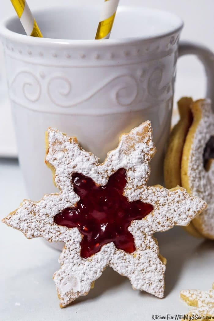 A linzer cookie snowflake leaned against a white coffee cup