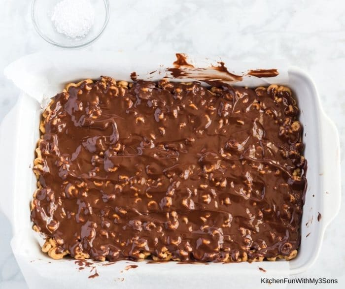 Chocolate mixture being spread over the top of homemade cereal bars