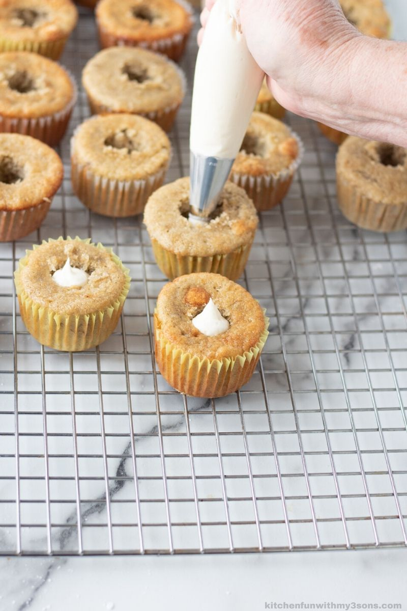 Filling banana cupcakes with banana cream cheese frosting