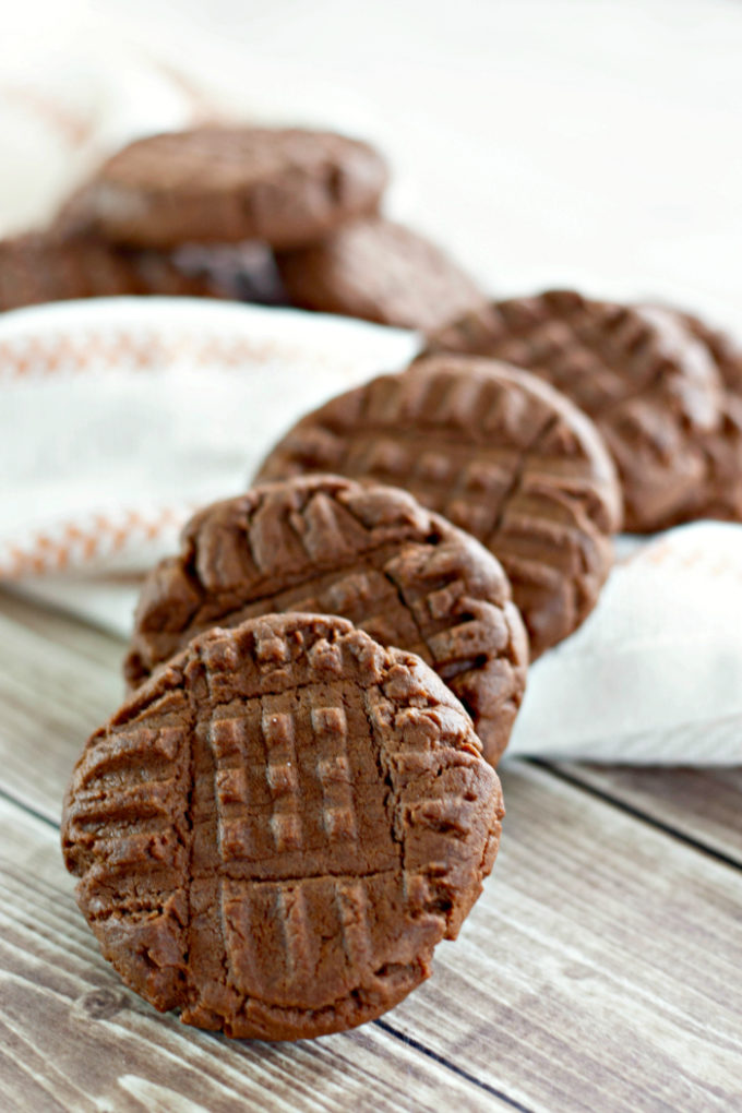 Chocolate Peanut Butter Cookies on a light wood table and white towel with brown trim