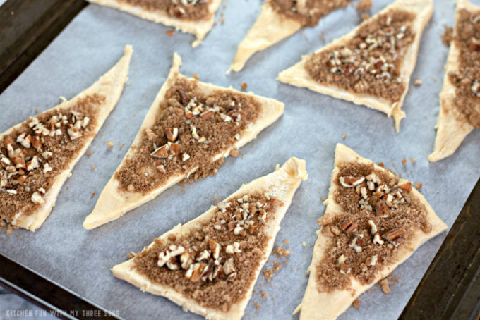 topping crescent roll triangles with apple pie spice, brown sugar, and chopped pecans