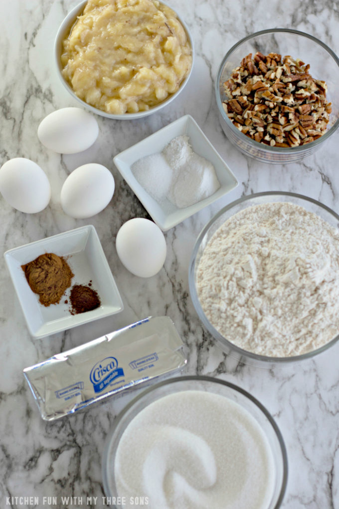 Mashed banana, chopped pecans, eggs, flour, Crisco, and sugar in glass bowls on a marble counter