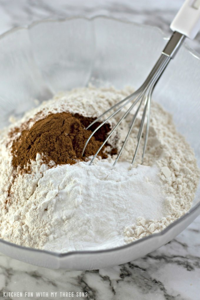 Whisking together flour, cinnamon, and baking powder in a clear bowl