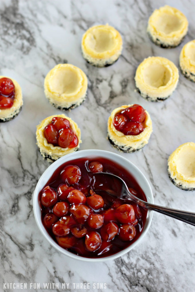 topping mini cheesecakes with cherry pie filling on a marble countertop
