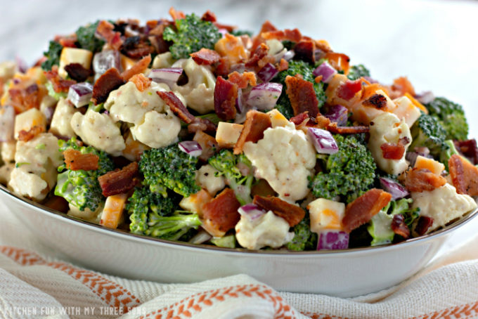 Low Carb Broccoli Salad in a white bowl with a silver rim set on a brown and white napkin