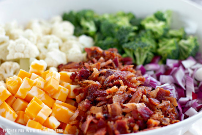 cheese cubes, crumbled bacon, chopped purple onions, broccoli, and cauliflower in a large mixing bowl