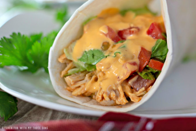 Slow Cooker Cheesy Chicken Tacos in a soft flour tortilla