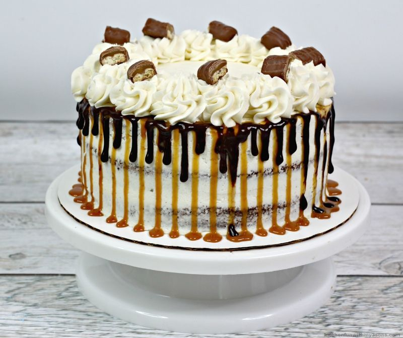 cholate layer cake with chocolate and caramel dripping over sides with twix candy bars