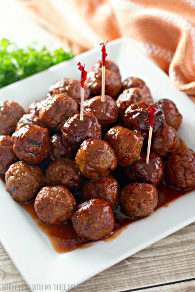 Easy Grape Jelly Meatballs for a Crowd on a white platter with toothpicks