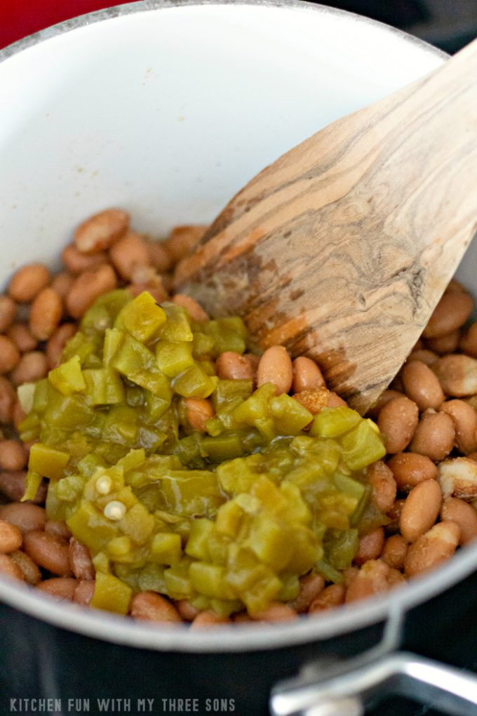 pinto beans in a white pot with green chiles