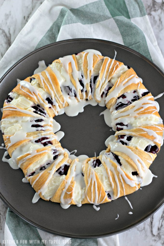 Raspberry Cheese Danish Ring on a pizza pan with a green and white towel