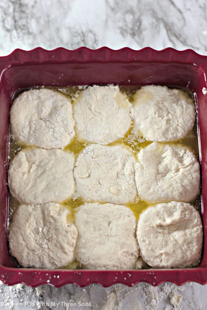 biscuit dough in butter in a square baking dish