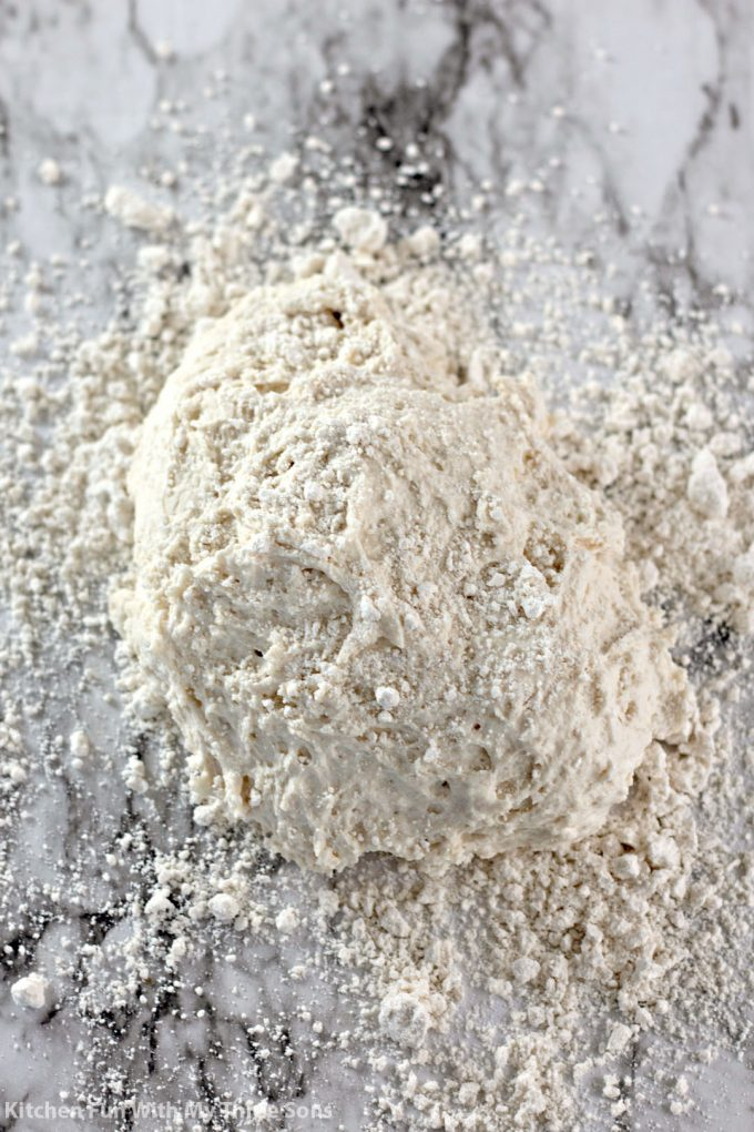 a ball of biscuit dough on a floured marble counter