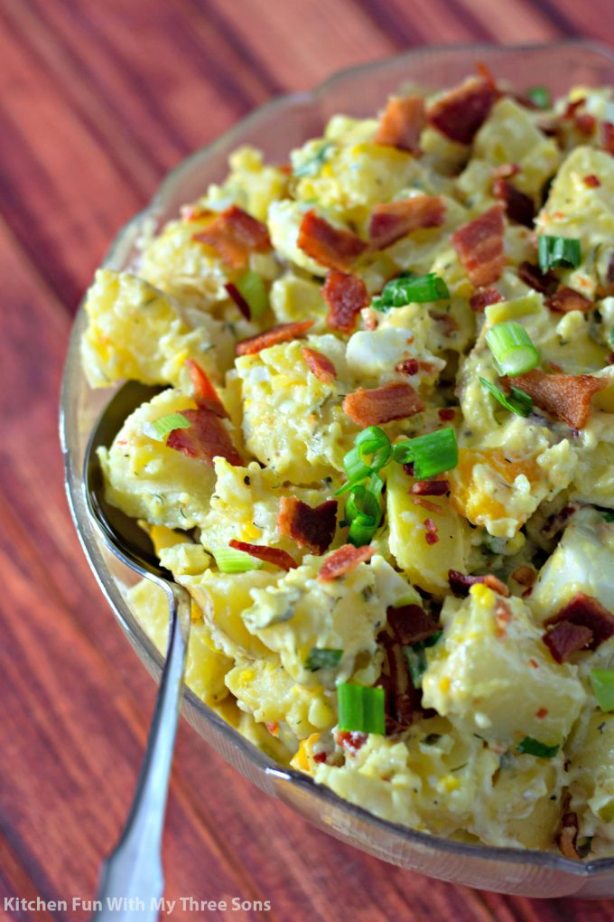 Bacon Potato Salad Recipe in a clear bowl on a wood table