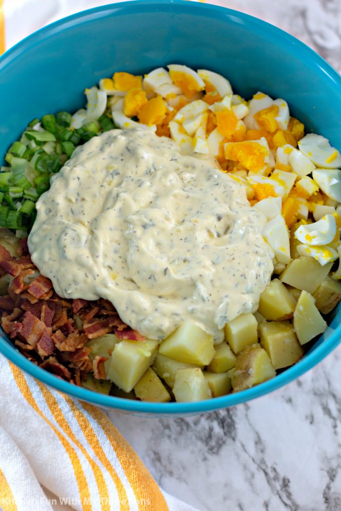 mixing together boiled potatoes, hardboiled eggs, green onions, bacon, and homemade dressing in a teal bowl