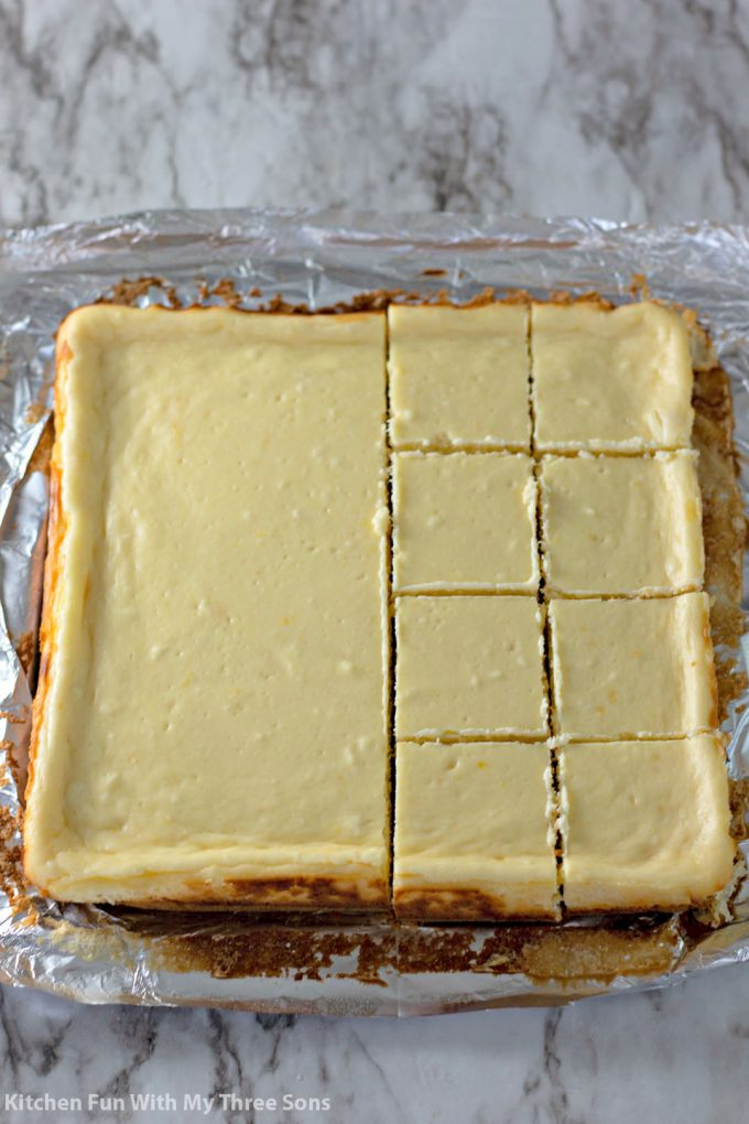 cutting the lemon cheesecake into square bars