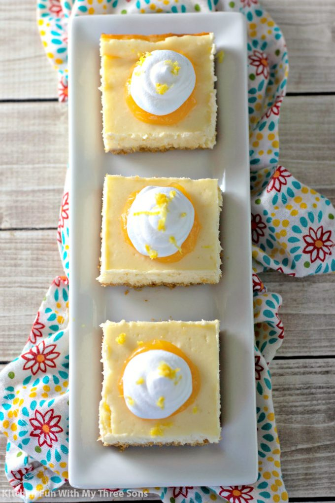 Easy Lemon Cheesecake Bars on a white platter with a flower print napkin