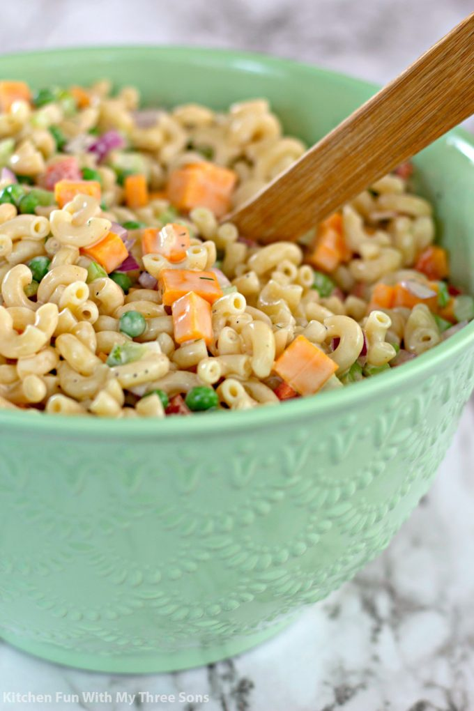 mixing Easy Macaroni Salad Recipe in a mint green bowl with a wooden spoon