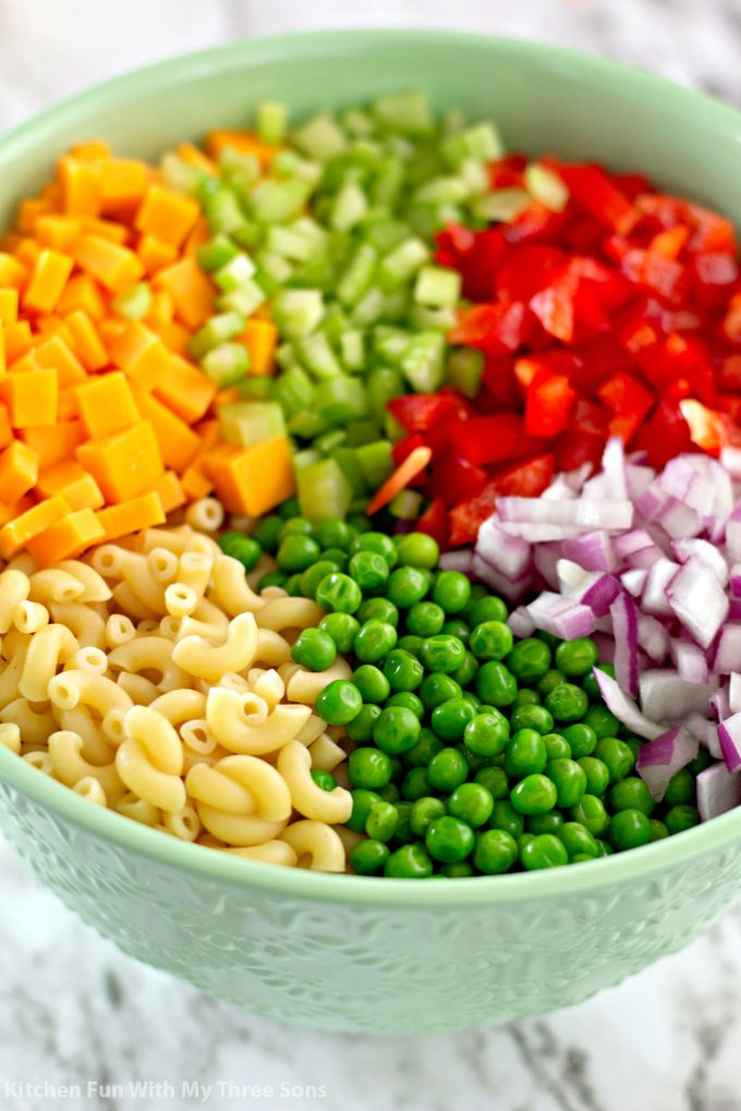 mixing together macaroni, cheese, bell pepper, peas, celery, and red onion in a mint green bowl