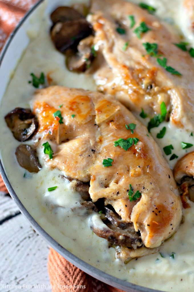 Garlic Butter Stuffed Chicken nestled in cream sauce with fresh chopped parsley