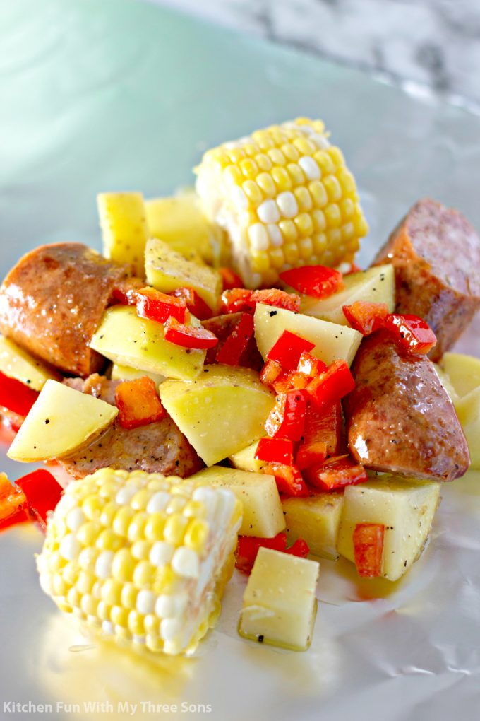 corn on the cob, potatoes, and kielbasa on a sheet of foil