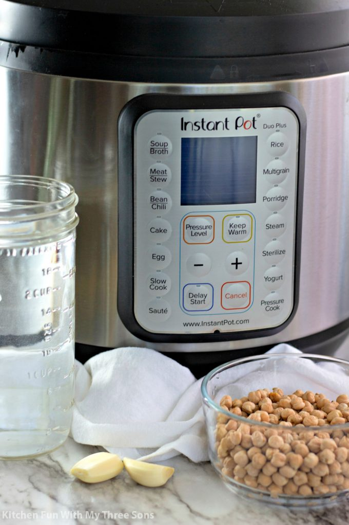 an Instant Pot with water, garlic, and garbanzo beans