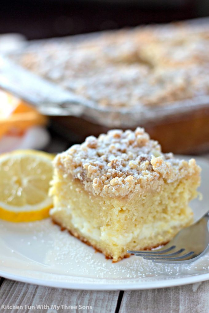 a slice of Lemon Cream Cheese Coffee Cake on a white plate with a lemon