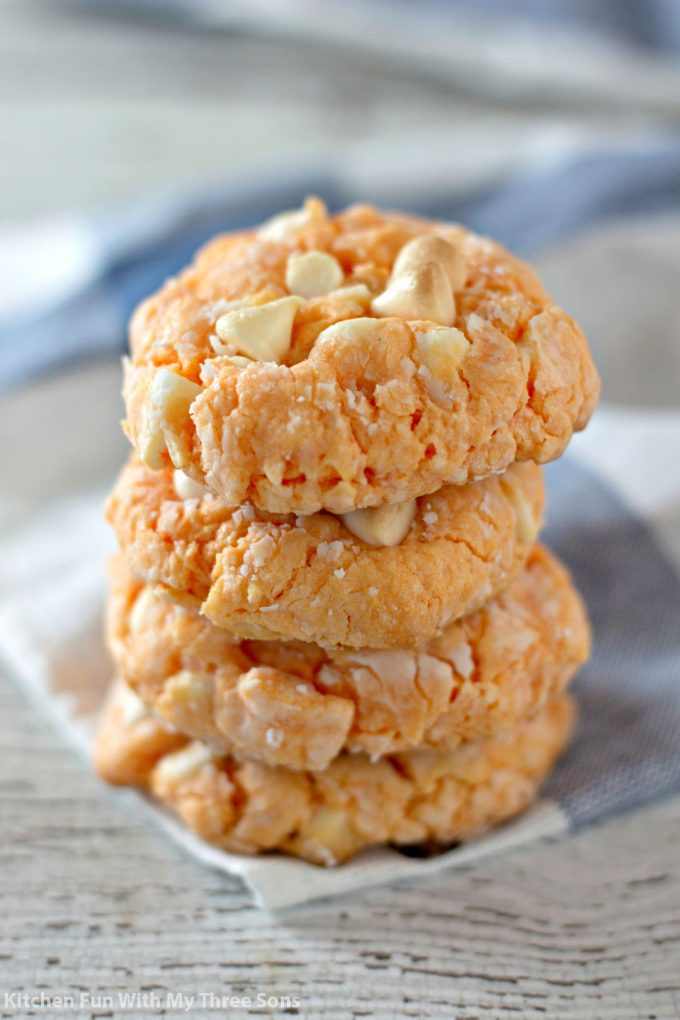 a stack or Orange Creamsicle Cake Mix Cookies on a blue and white napkin