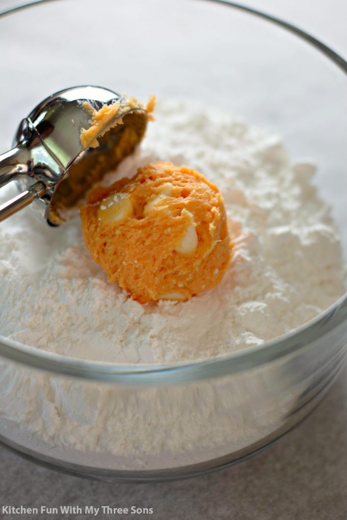 scooping the orange dough into a clear bowl filled with powdered sugar