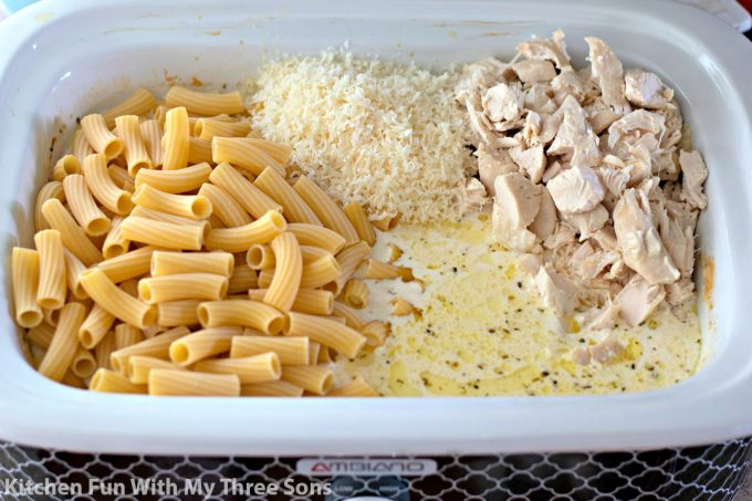 pasta, chicken, cheese, and sauce in a slow cooker