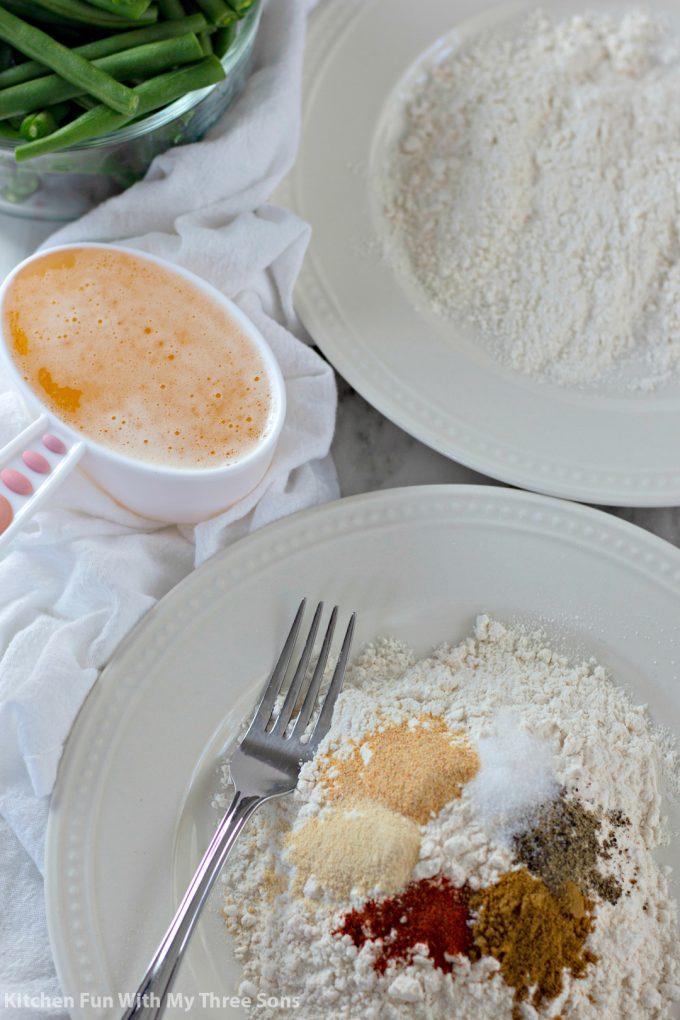 battering fresh green beans in seasoned flour and beer batter