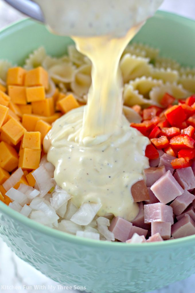 pouring homemade dressing into the bowl of salad ingredients