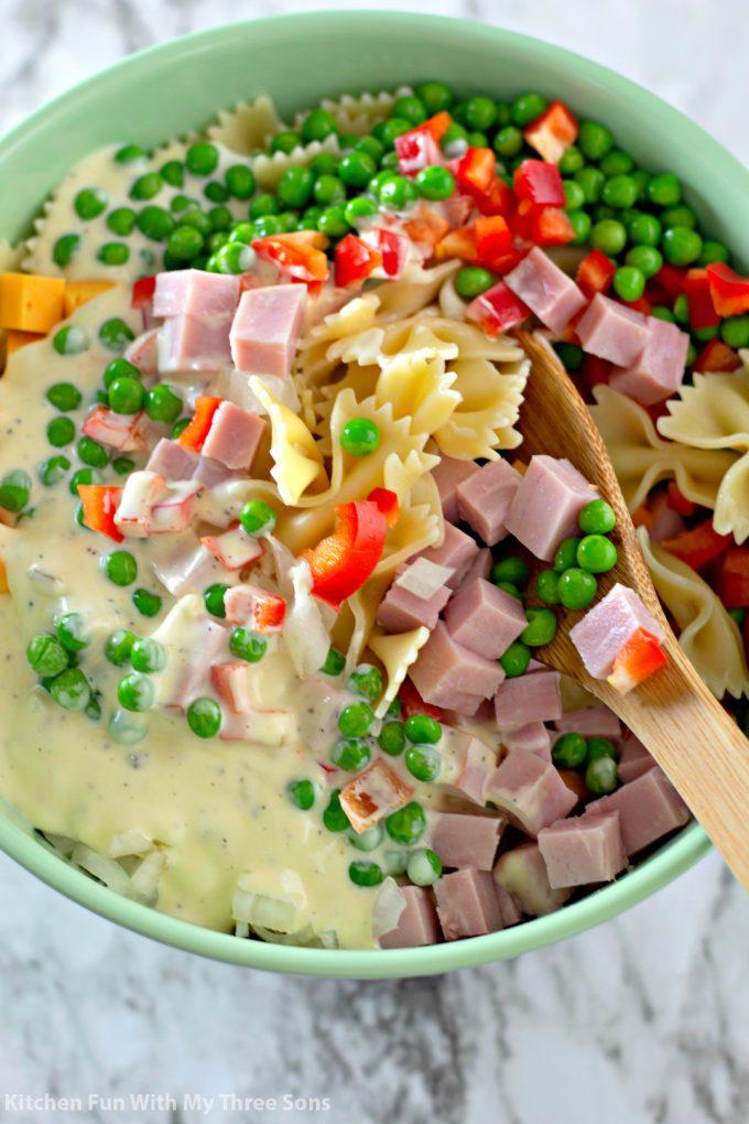 stirring pasta salad in a mint green bowl