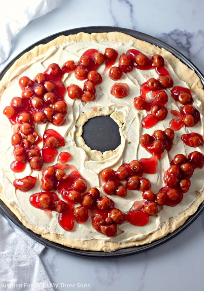 pouring cherries over the cream cheese layer
