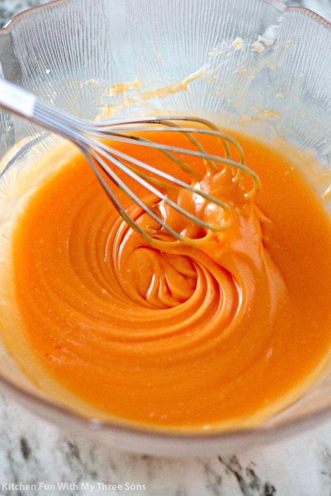 whisking white chocolate orange ganache in a clear bowl