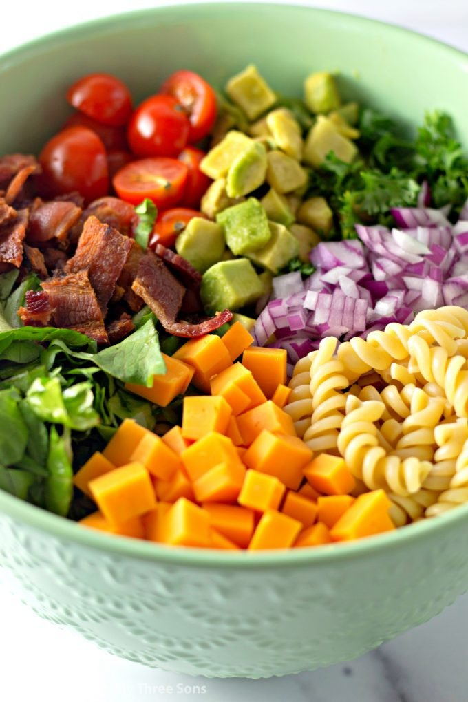 rotini pasta, tomatoes, avocado, bacon, parsley, lettuce, and cheese in a mint green bowl