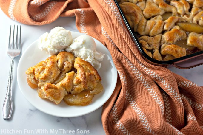 Easy Apple Dumpling Casserole with ice cream and a rust colored napkin