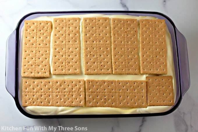 topping the cake with graham crackers