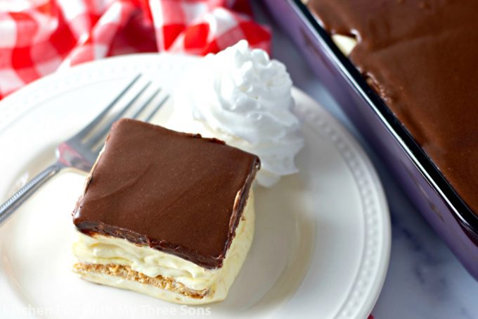 No Bake Eclair Cake on a white plate with whipped cream