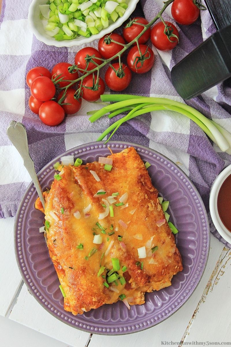 Air Fryer Rotisserie Chicken Enchiladas on a serving plate with a side of cherry tomatoes.