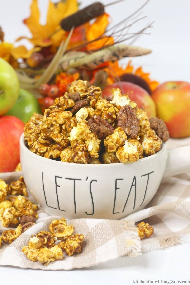Apple Pie Bourbon Flavored Popcorn Mix with apples, twigs and leaves behind it.