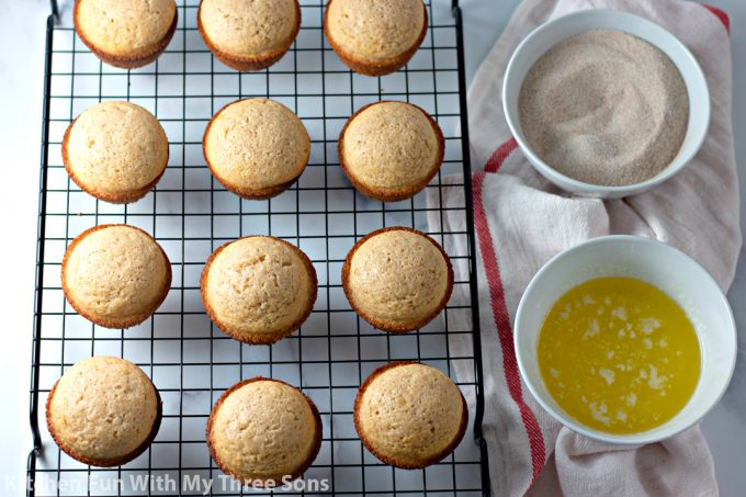 muffins cooling on a wire cooling rack next to butter and cinnamon sugar