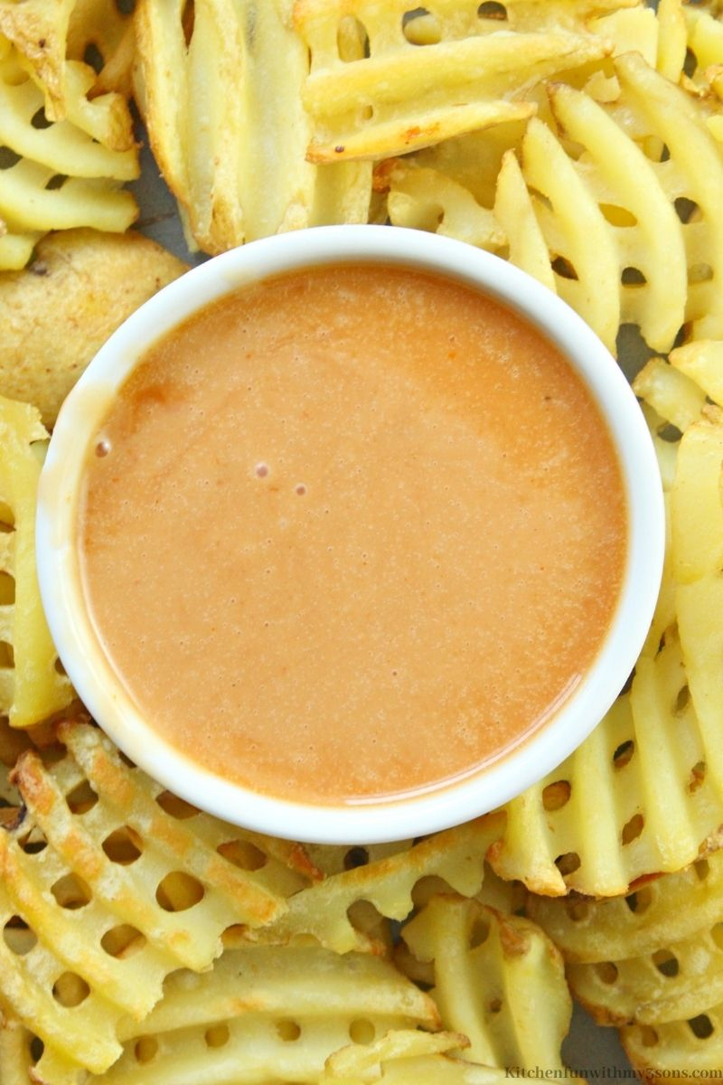 Chick Fil A dipping sauce surrounded by fries.