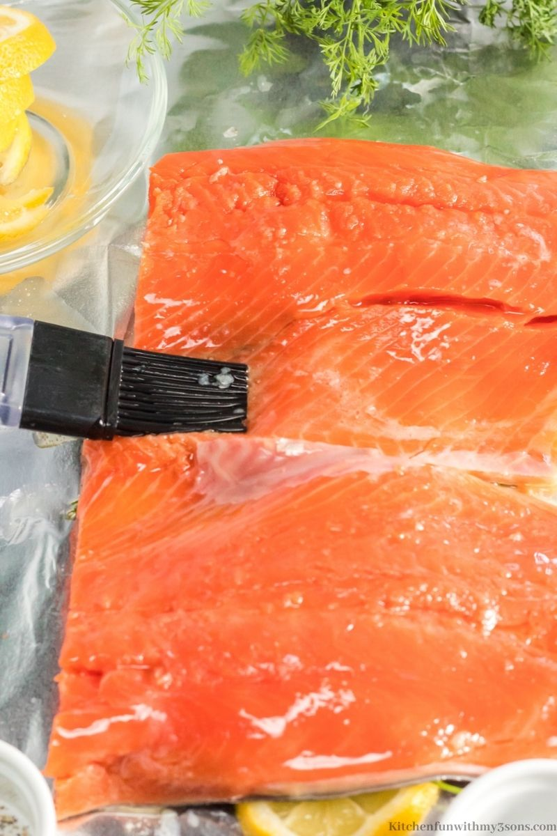 Brushing melted butter on the salmon in the foil.
