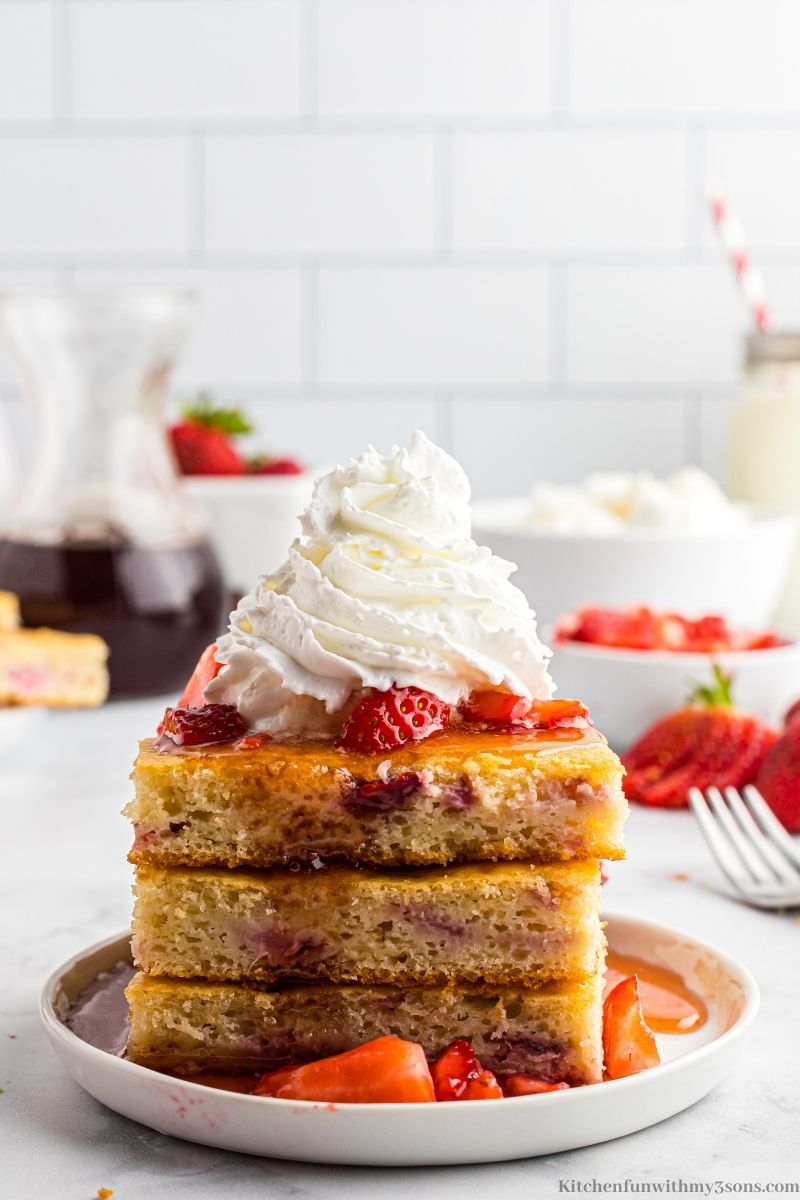 Pancakes on a serving plate with more strawberries and whipped cream on top.