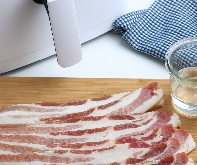 raw bacon on a cutting board