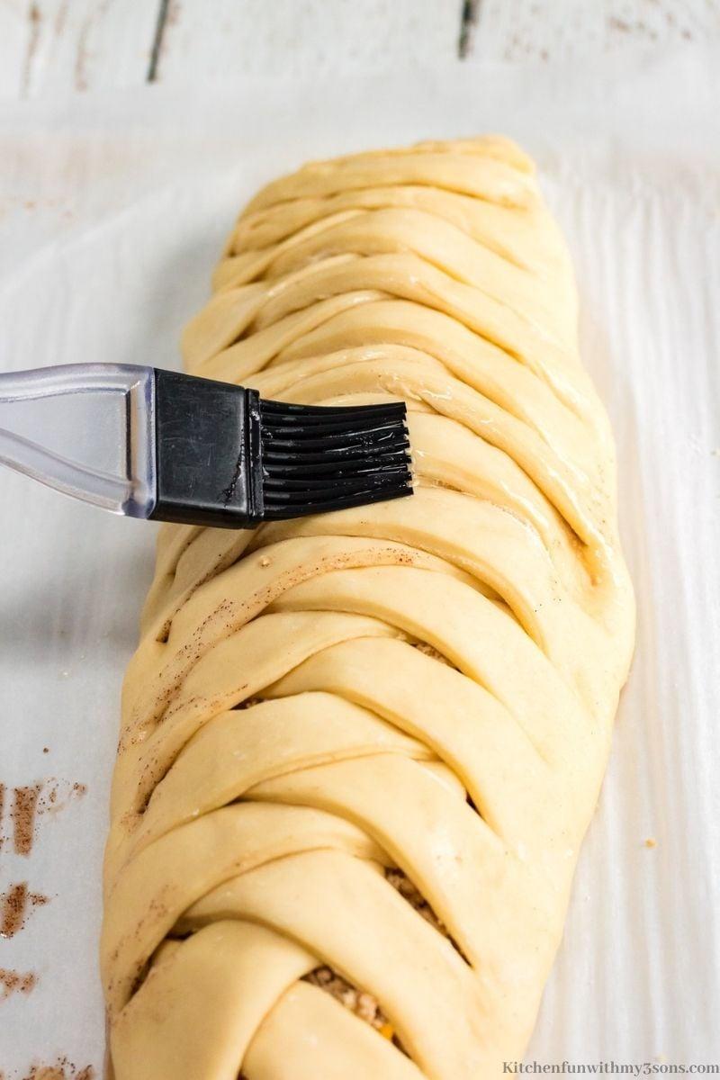 Brushing egg whites on the dough.