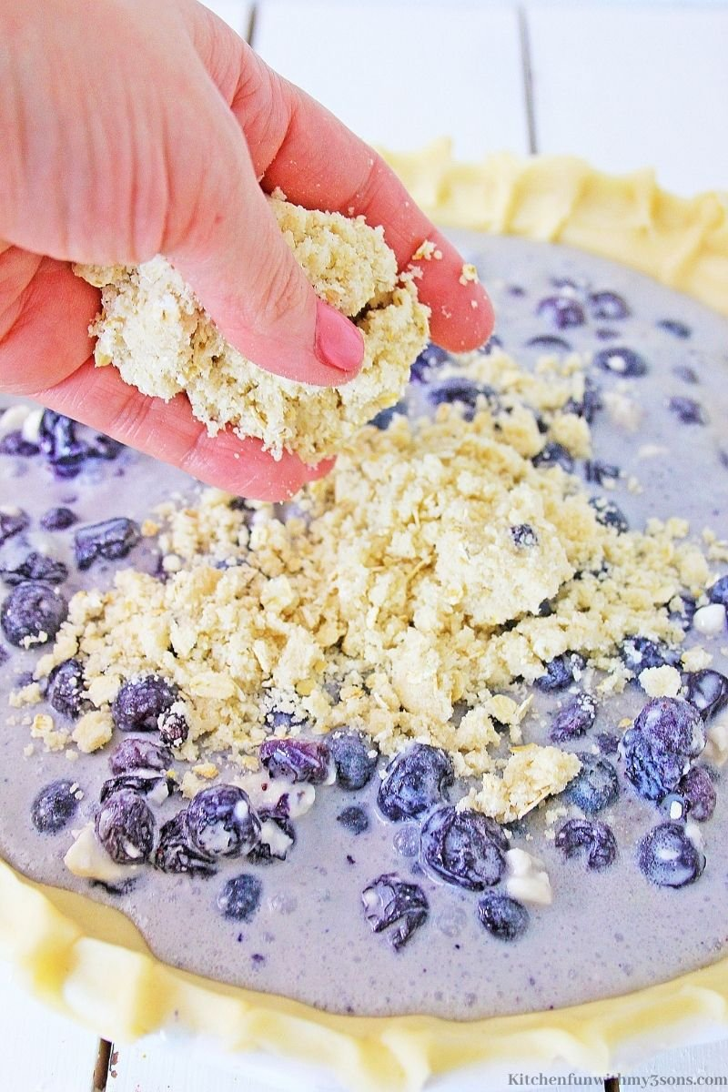 Adding the crumbles over the pie filling.